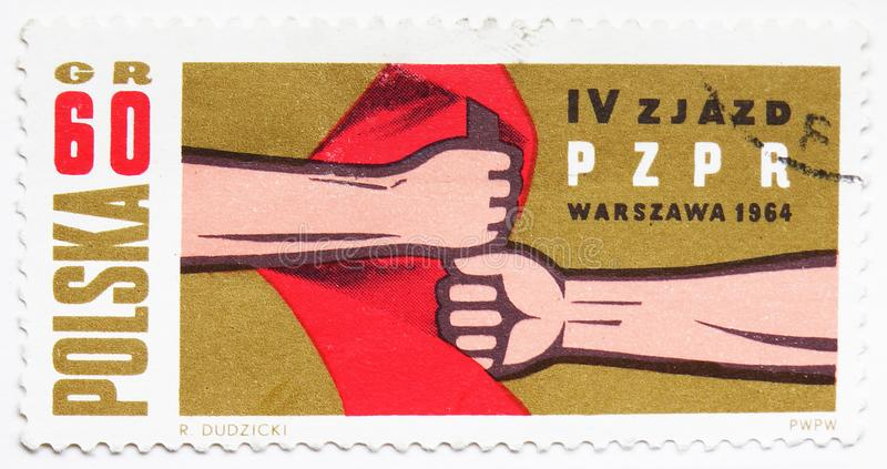 Hands Holding Red Flag, 4th Congress of the Polish United Workers Party serie, circa 1964. MOSCOW, RUSSIA - JULY 15, 2019: Postage stamp printed in Poland shows royalty free stock photography