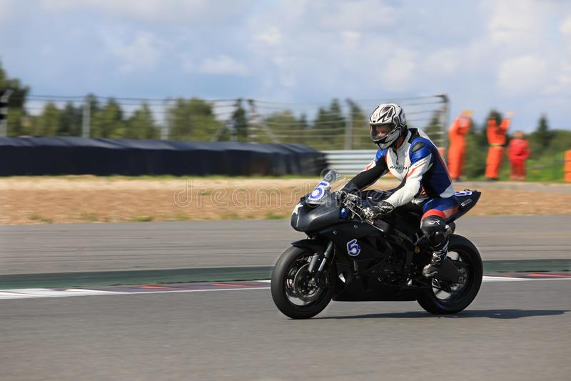 Racing bike rider racing at high speed. MOSCOW, RUSSIA - JULY 21, 2019: Racing bike rider in helmet racing at high speed on race track during the championship of stock photos