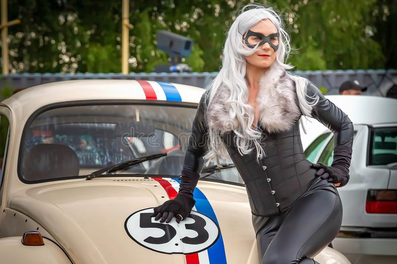 Moscow, Russia: July 06, 2019: A restored Volkswagen beetle stylized with number 53. A catwoman dressed in black leaned on the stock photos