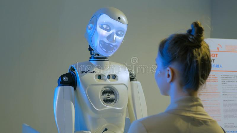 Funny humanoid robot with display face talking with woman. MOSCOW, RUSSIA - July 30, 2018: Robostation - future exhibition. Funny humanoid robot with display royalty free stock photography