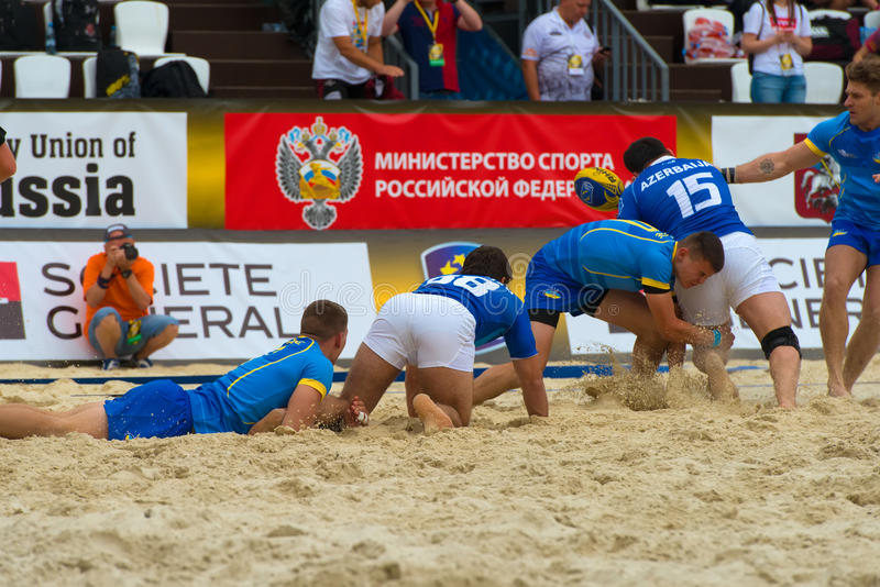 All fell. MOSCOW, RUSSIA - JULY 22-23, 2017: Rugby players in action at the on European Beach Fives Rugby Championship 2017 in the match Ukraine blue vs royalty free stock image