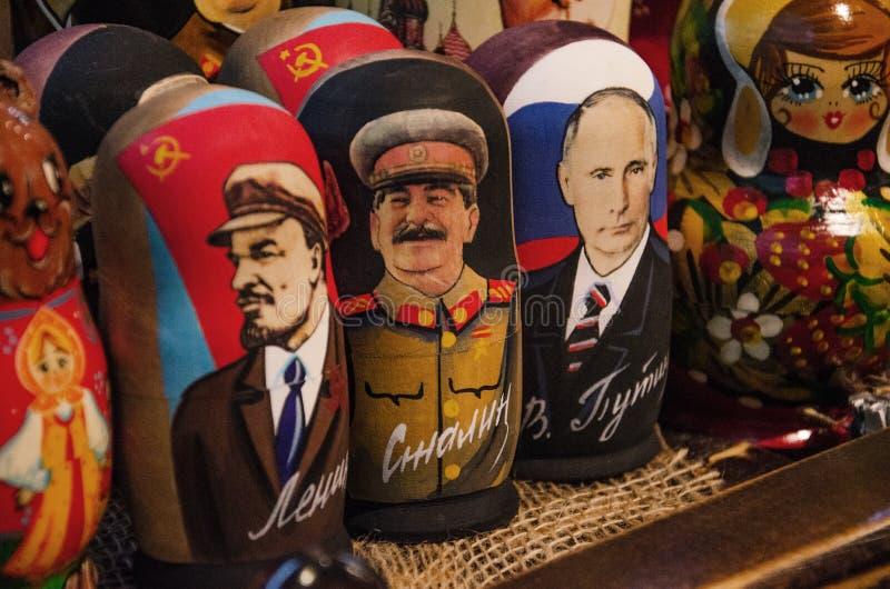 Russian traditional nested dolls. Dolls have a portrait of Vladimir Lenin, Vladimir Putin and Joseph Stalin. Modern caricatures royalty free stock photo
