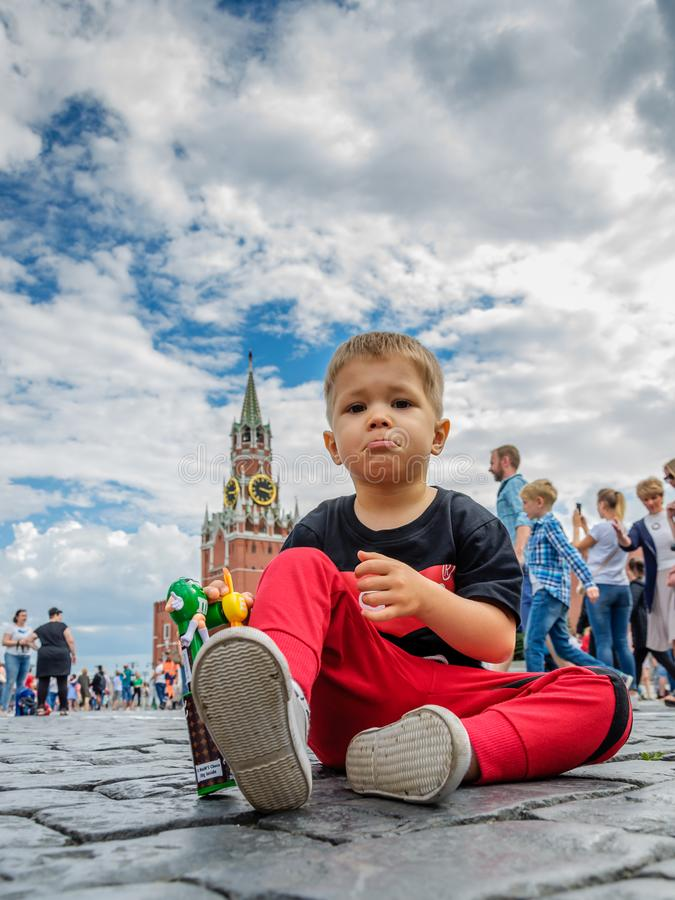 Moscow, Russia - July 7, 2018: unsatisfied, not happy boy sits on Red Square paving stones, tourist or political concept royalty free stock image