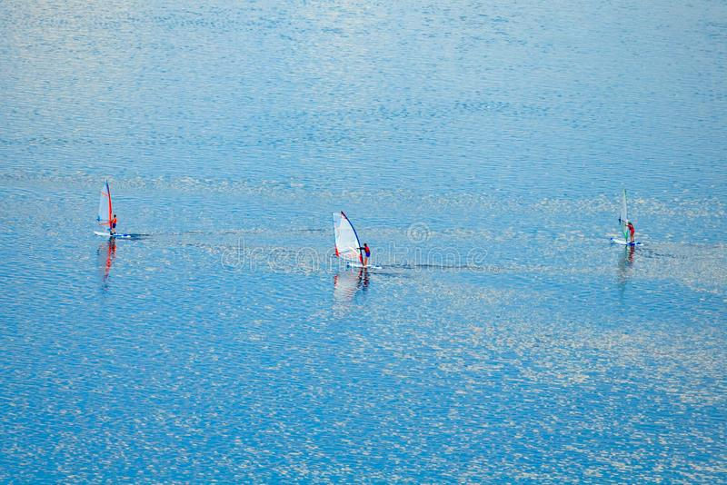 Aerial view on a windsurfers on the azure water. Moscow, Russia, june 2018: Aerial view on a windsurfers on the turquoise water royalty free stock photography
