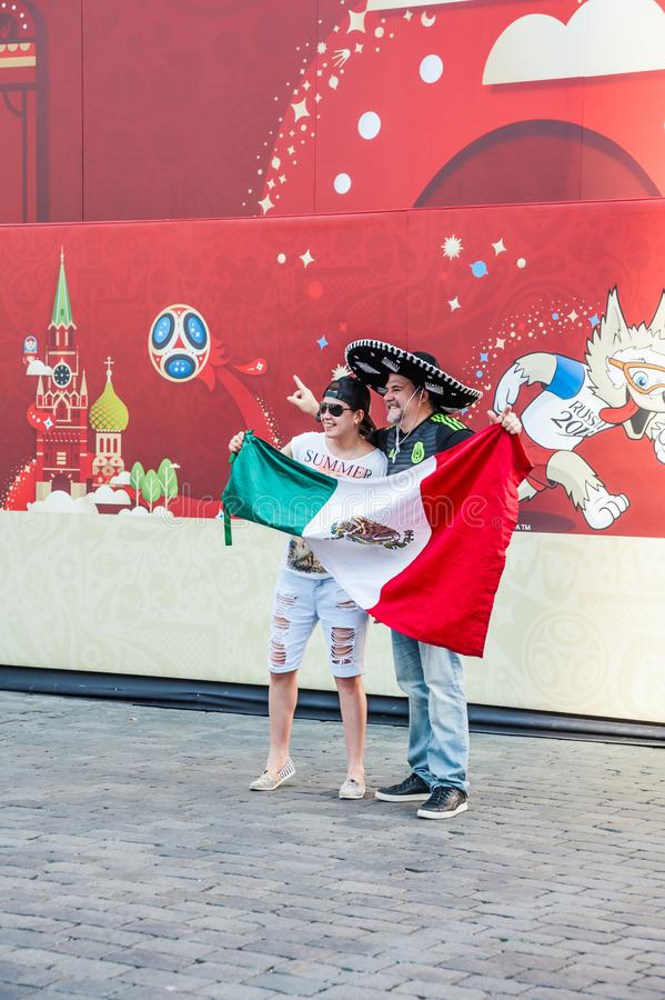 The 2018 FIFA World Cup. Mexican fans with flag photographed on the background of a banner. MOSCOW, RUSSIA - June 29, 2018: The 2018 FIFA World Cup. Mexican fans royalty free stock photos