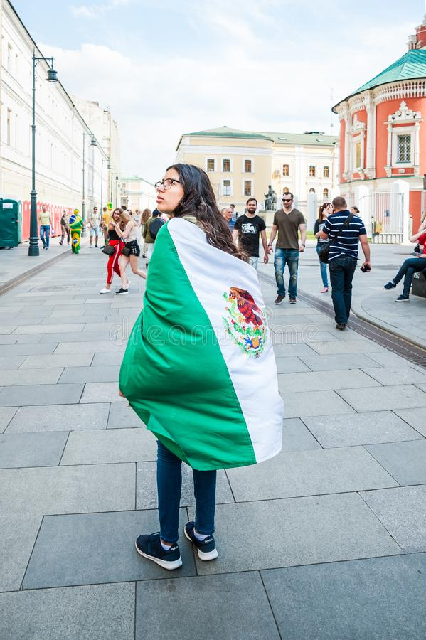 The 2018 FIFA World Cup. Mexican girl, the football fan with Mexico flag on her shoulders on Bogoyavlensky lane. MOSCOW, RUSSIA - June 29, 2018: The 2018 FIFA stock photography