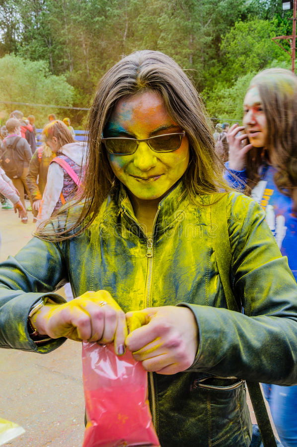 Moscow, Russia - June 3, 2017: Girl, smeared with yellow paint during expressive Holi-battle open pack with pink powder stock photography