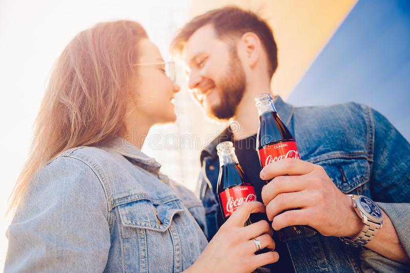 Moscow, Russia - June 27, 2019: happy couple hugging smiles and holds Coca Cola glass bottle soda in hand, sunset stock photos