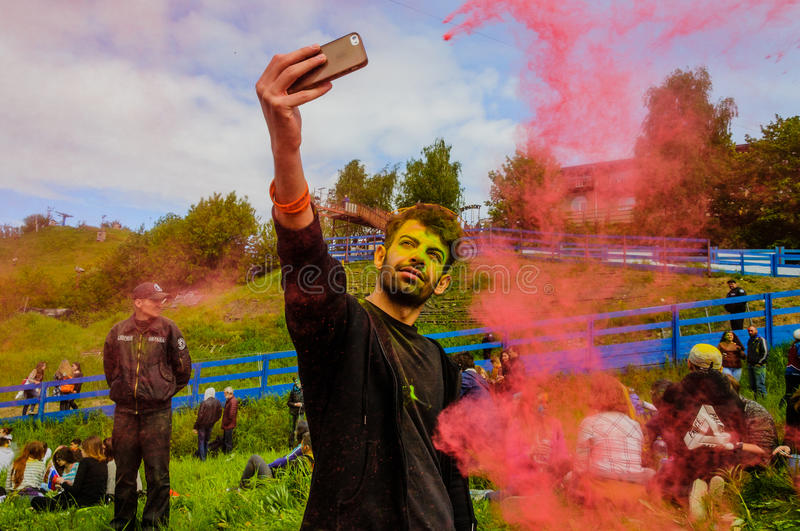 Moscow, Russia - June 3, 2017: Man makes selfie in epicenter of colorful explosion pink powder at Holi Colors Festival royalty free stock photography