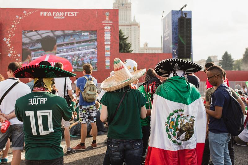 MOSCOW, RUSSIA - JUNE 2018: Mexican fans with national flag and sombrero watching match Mexico - South Korea. MOSCOW, RUSSIA - JUNE 2018 Mexican fans with stock photos
