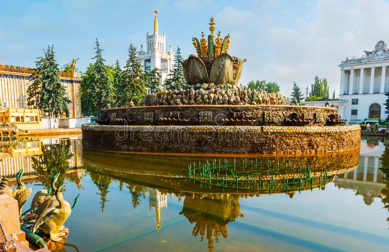 The ornate Stone Flower Fountain, VDNH, Moscow. MOSCOW, RUSSIA - JUNE 29, 2013: The ornate Stone Flower Fountain with its pure reflection and the golden spire of royalty free stock images