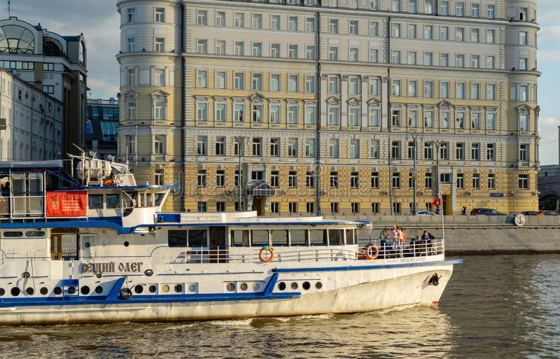 Pleasure boat with people on board sailing along Moskva riveragainst Hotel Baltschug Kempinski on Raushskaya Embankment. Moscow, Russia - June 16, 2019: Pleasure royalty free stock image