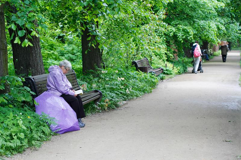 Senior woman sitting on wooden bench and reading a book in botanical garden `Aptekarsky garden` in Moscow. Moscow, Russia - June 05, 2017: Senior woman sitting stock photography