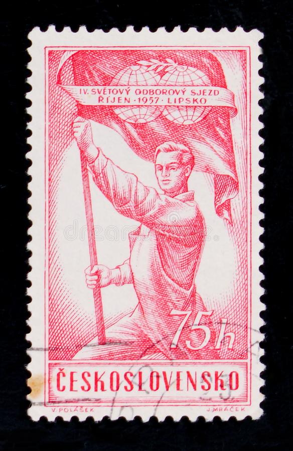 MOSCOW, RUSSIA - JUNE 20, 2017: A stamp printed in Czechoslovakia shows a worker holding a red flag, devoted to the IV World Cong. Ress of Trade Unions , circa stock photography