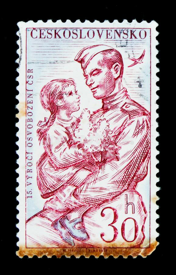 MOSCOW, RUSSIA - JUNE 20, 2017: A stamp printed in Czechoslovakia shows shows Soldier holding child, circa 1960 stock image