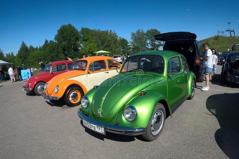 Moscow, Russia - June 01, 2019: Volkswagen beetle Kaefer  parked in row on the open parking on the street. Green, orange and red stock photography