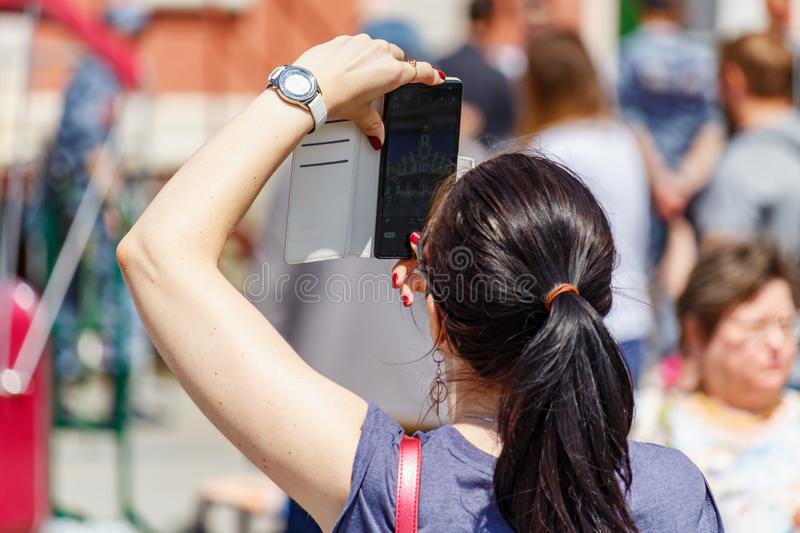 Moscow, Russia - June 02, 2019: Woman takes a photo on the modern smartphone on Red Square in Moscow at sunny summer day closeup stock images