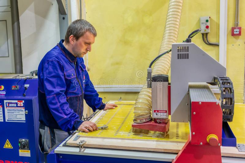 A worker measures a part made on a milling machine. Stage control of finished products. Moscow, Russia - june 18, 2019: A worker measures a part made on a stock photos