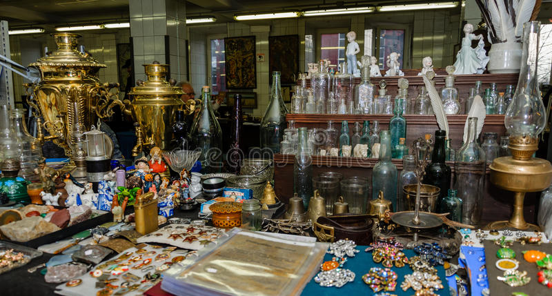 Moscow, Russia - March 19, 2017: Antique market with old bottles of different sizes, porcelain figurines and bronze. Moscow, Russia - March 19, 2017: Table at royalty free stock photos