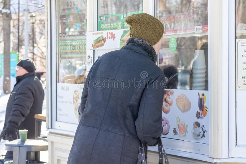 MOSCOW, RUSSIA - MARCH 02, 2019: A man buying street fast food and hot drinks in the stall during the stroll in a city park in stock photography