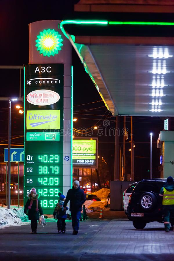 MOSCOW, RUSSIA - MARCH 20, 2018: A man with two children walks past the BP Connect gas station on the highway in a busy Moscow. District in the evening. The LED royalty free stock image
