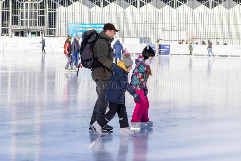 MOSCOW, RUSSIA- MARCH 02, 2019: People wearing winter clothes, father and his children skating on a winter skating rink, family. Leisure and sport activity on royalty free stock images