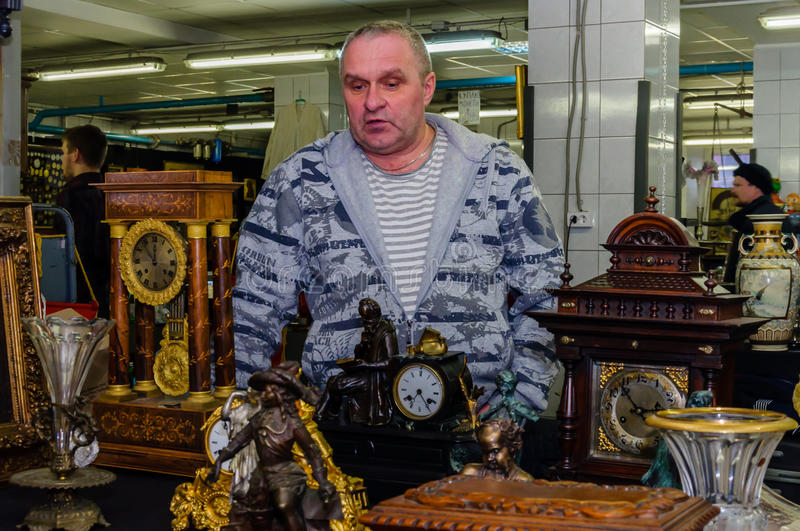 Moscow, Russia - March 19, 2017: Seller of vintage richly decorated collection mantel clocks at an antic market royalty free stock photo