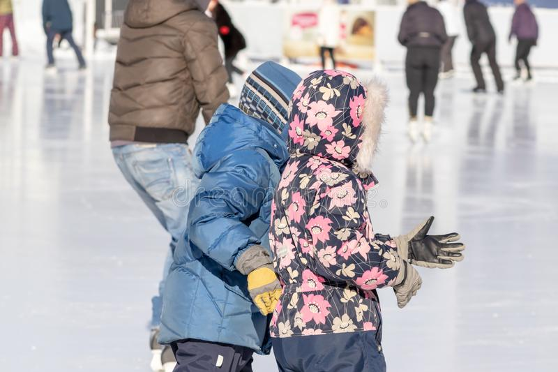 MOSCOW, RUSSIA- MARCH 02, 2019: Two children wearing winter clothes skating on a winter skating rink, family leisure and sport. Activity on christmas vacations stock photography