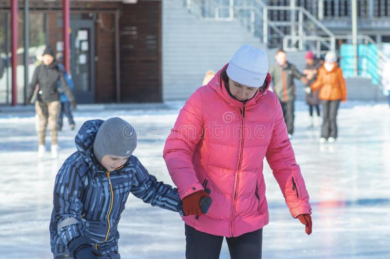 MOSCOW, RUSSIA- MARCH 02, 2019: Woman teaching her child to skate on a winter skating rink, family leisure and sport activity on. Christmas vacations and stock photos