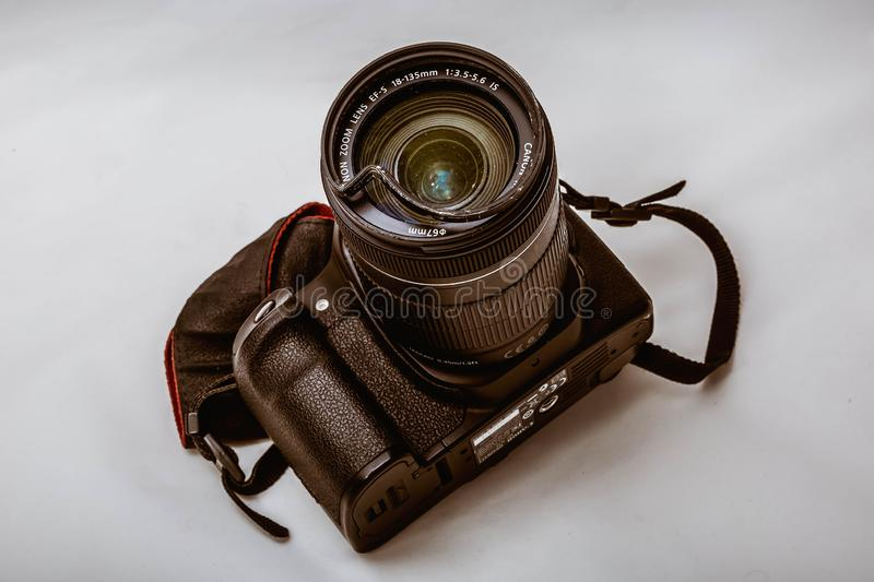 Moscow, Russia - May 13, 2019: Broken reflex dslr digital camera Canon, with a damaged lens 18-135mm on a gray background. The royalty free stock images