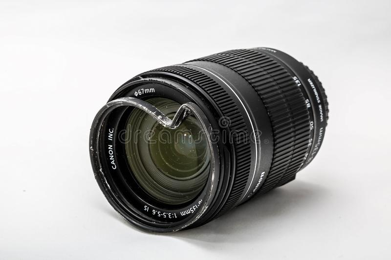 Moscow, Russia - May 13, 2019: Canon zoom tele foto lens 18-135mm with a broken protective glass filter on a white background. stock images