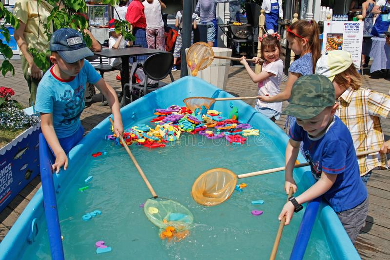 Children with butterfly nets catch toys in the boat at the Fish Week festival in Moscow royalty free stock image