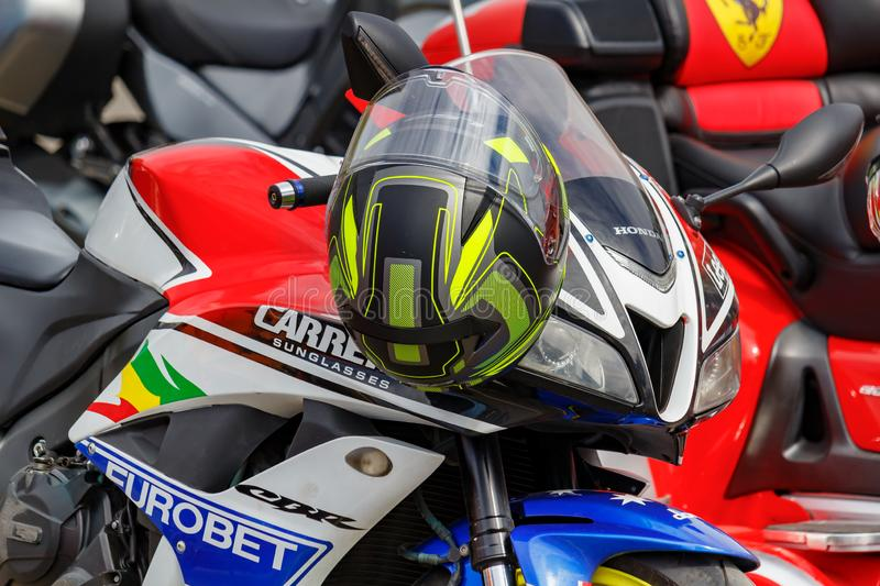 Moscow, Russia - May 04, 2019: Colored helmet on the handlebar of Honda sports motorcycle closeup. Moto festival MosMotoFest 2019 stock photo