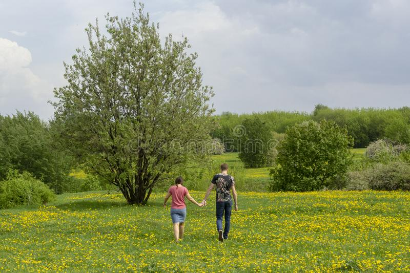 Moscow, Russia – May 15, 2019: A couple of young people go through the meadow royalty free stock photos