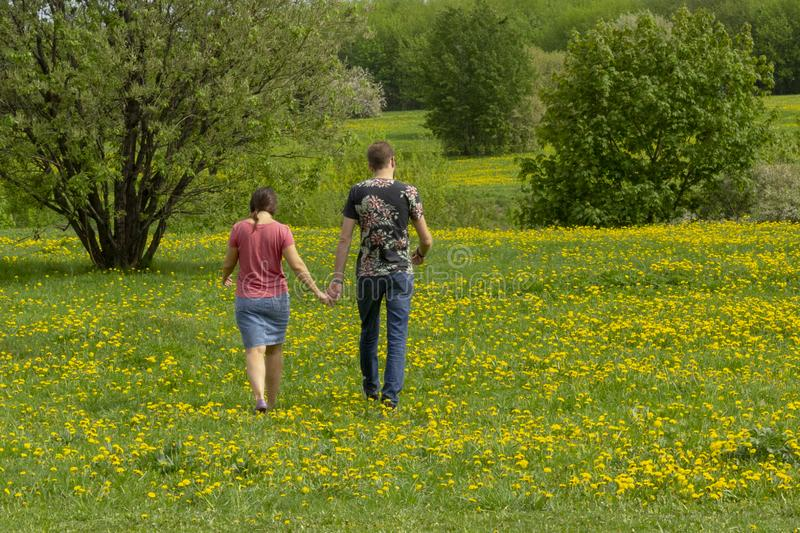 Moscow, Russia – May 15, 2019: A couple of young people go through the meadow royalty free stock photography