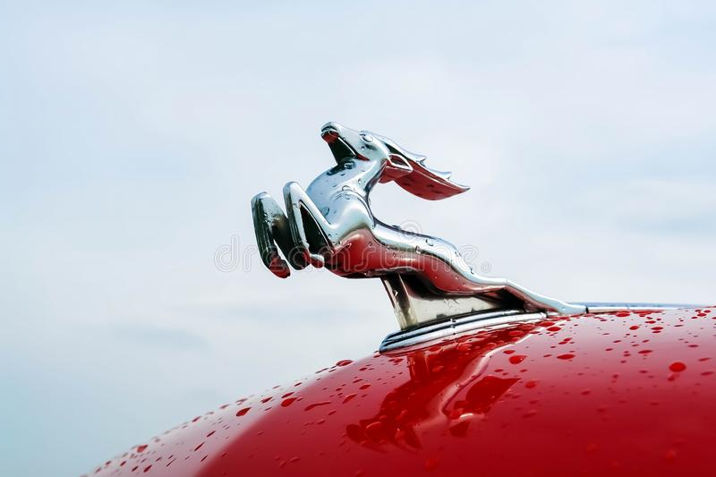 Moscow, Russia - May 25, 2019: A deer on the red hood of a Gaz-21 Volga car against the sky. Russian retro car royalty free stock image