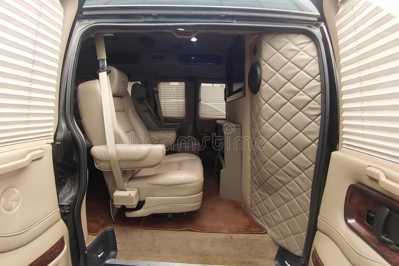 Moscow, Russia - May 2, 2019: GMC Savana/ Chevrolet Express tuning interior. Custom tuned interior with telephone, sound system. And tv. White leather inside of royalty free stock photo