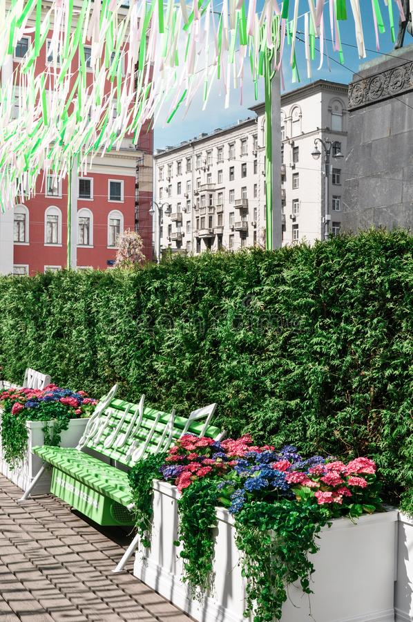 Moscow, Russia - May, 05, 19. Music bench, beautiful flowers and pink,green, white ribbons fluttering in the wind on. Tverskaya square. Moscow spring from stock images
