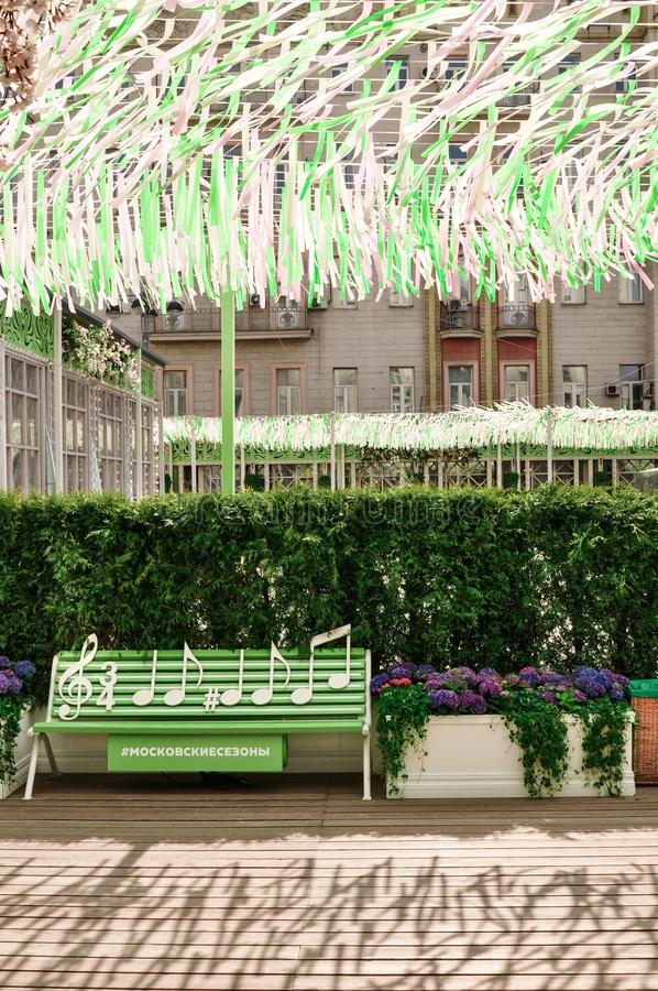 Moscow, Russia - May, 05, 19. Music bench, beautiful flowers and pink,green, white ribbons fluttering in the wind on. Tverskaya square. Moscow spring from stock photos