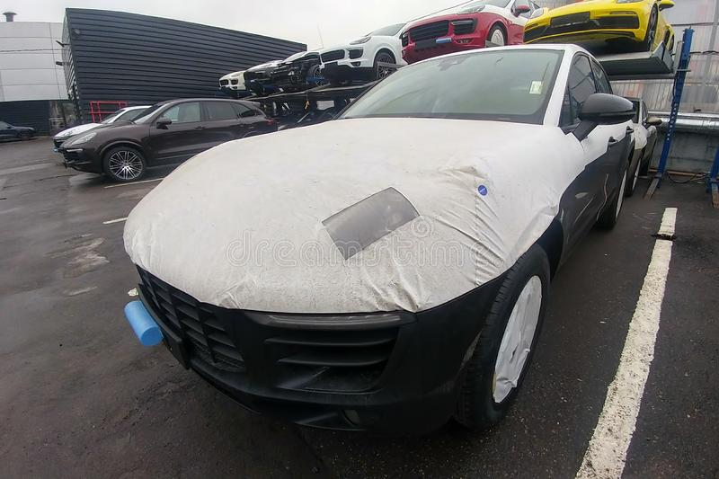 Moscow, Russia - May 08, 2019: New car arrived from factory for sale. Black car wrapped with shipping film. Macan paint scratches vehicles covered protect stock photos