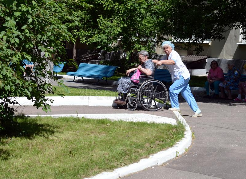 The nurse is rolling an elderly woman in a wheelchair on the territory of the hospital of veterans of wars. MOSCOW, RUSSIA - MAY 27, 2015:The nurse is rolling royalty free stock photo
