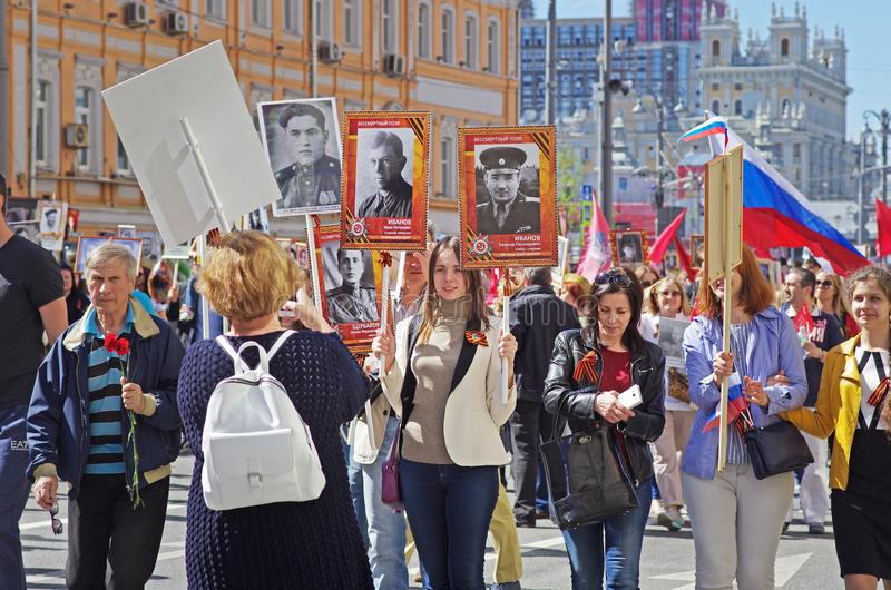 People hold portraits of their relatives in the action `Immortal regiment` on Victory day in Moscow. Moscow, Russia - May 09, 2018: People hold portraits of stock photography