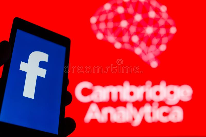 MOSCOW, RUSSIA - MAY 9, 2018: Smartphone in hand with logo of popular social network Facebook. Cambridge Analytica emblem stock images