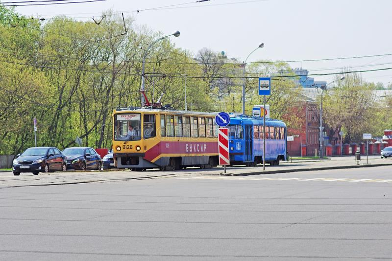 A special tram-tug tows a faulty tram along a city street in Moscow. Moscow, Russia - May 02, 2018: A special tram-tug tows a faulty tram along a city street in stock images