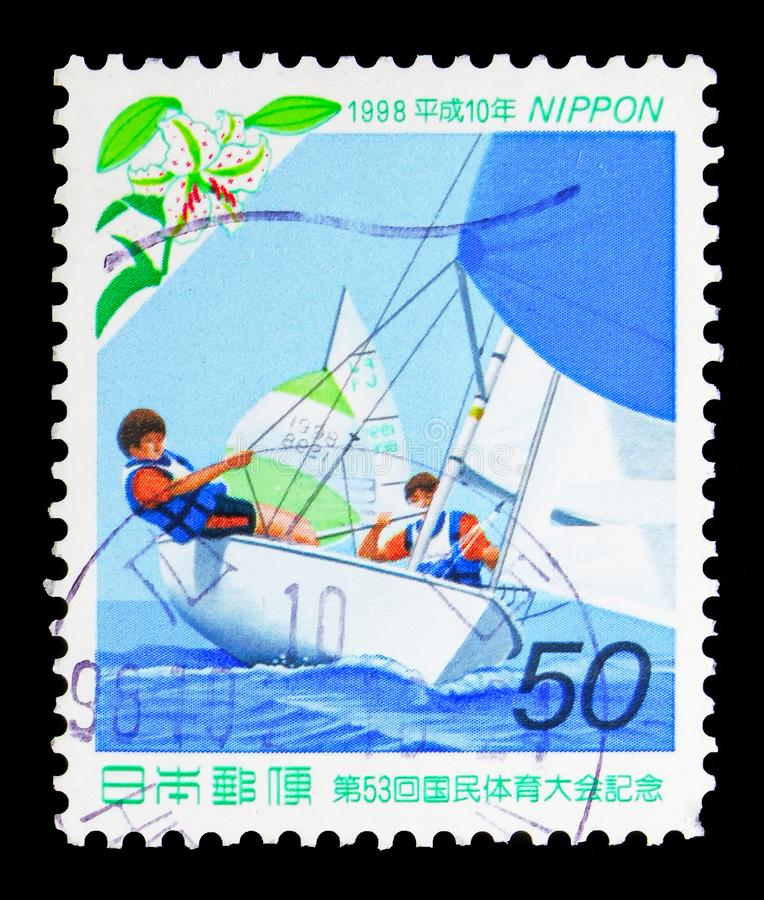 Racing Yacht (FJ Class) and Golden-banded Lily (Yamayuri), National Athletic Meeting serie, circa 1998. MOSCOW, RUSSIA - MAY 13, 2018: A stamp printed in Japan royalty free stock photo
