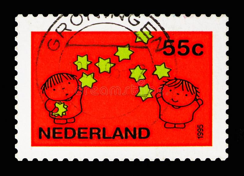 Children and stars, December stamps serie, circa 1995. MOSCOW, RUSSIA - MAY 13, 2018: A stamp printed in Netherlands shows Children and stars, December stamps royalty free stock photo