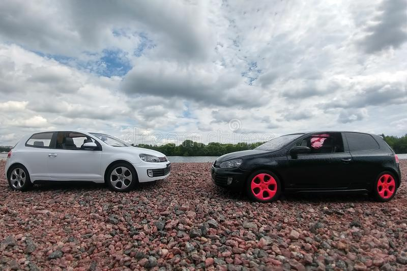 Moscow, Russia - May 03, 2019: Two toy cars Volkswagen golf mk6 stand on a pebble beach of Moscow river. White and black GTI stand stock image