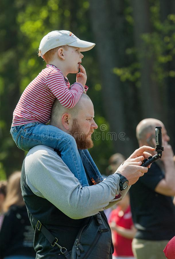 Man with kid on a shoulders look at mobile phone royalty free stock photo