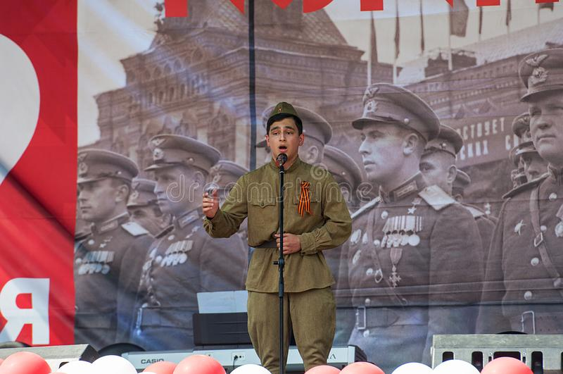 Man in military uniform sing a song on a scene stock image