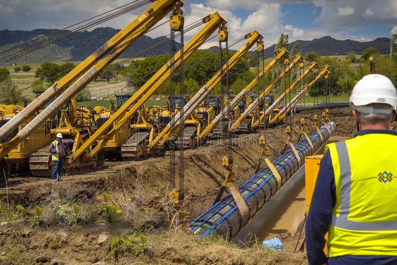 Construction work on the installation of the pipeline. Gas pipeline installation and construction. Moscow, Russia - May 22, 2018: Workers in helmets on the royalty free stock photography